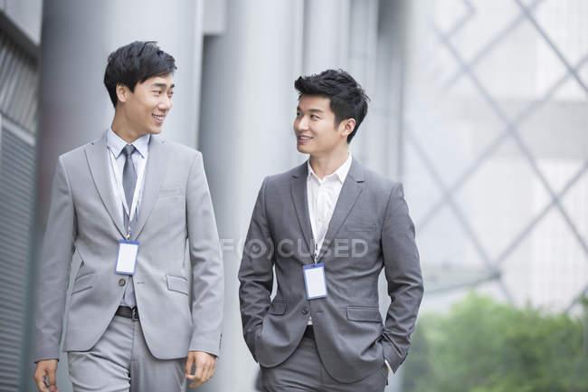 Empresários chineses caminhando e falando na rua — Fotografia de Stock
