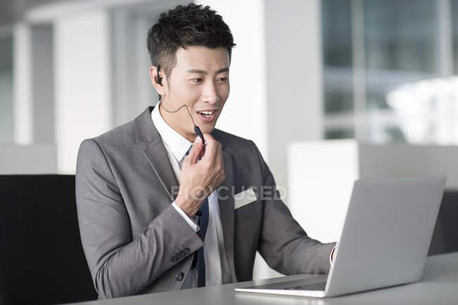 Gerente de venta chino con auriculares usando computadora portátil - foto de stock