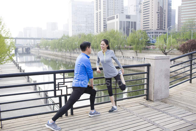 Mature chinese couple stretching in park — Stock Photo