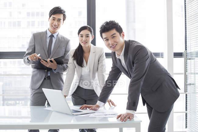 Les hommes d'affaires chinois utilisant un ordinateur portable en réunion — Photo de stock