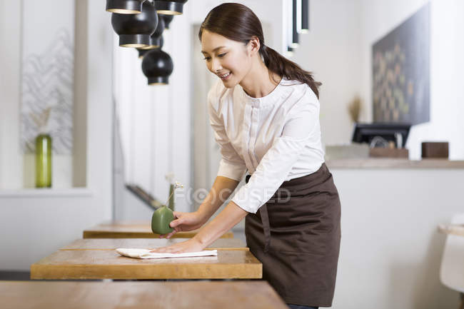 Chinese waitress wiping table in cafe — Stock Photo