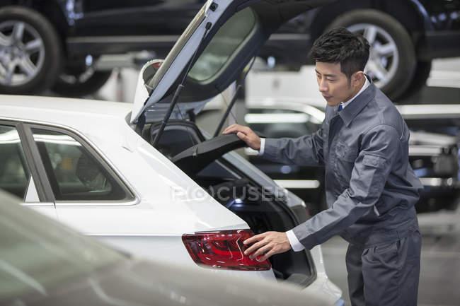 Garagiste chinois à la recherche dans le coffre de la voiture dans l'atelier de réparation — Photo de stock