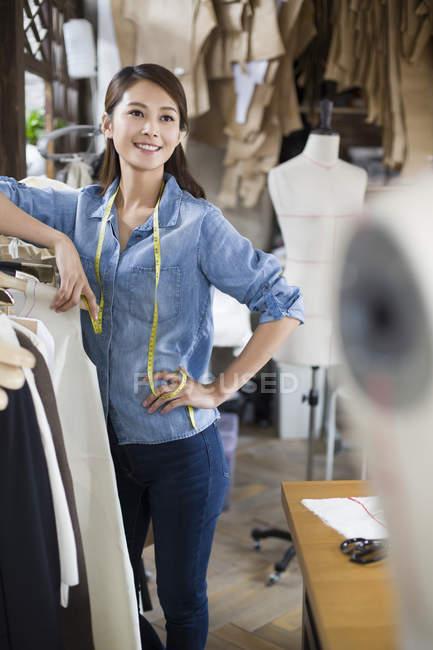 Китайський Дизайнер жіночого одягу стоячи в магазині одягу стійки — стокове фото