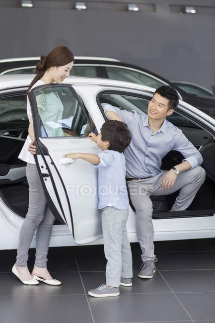 Chinese family sitting in new car in showroom — Stock Photo