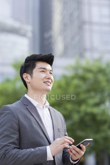 Chinese businessman looking away on street — Stock Photo