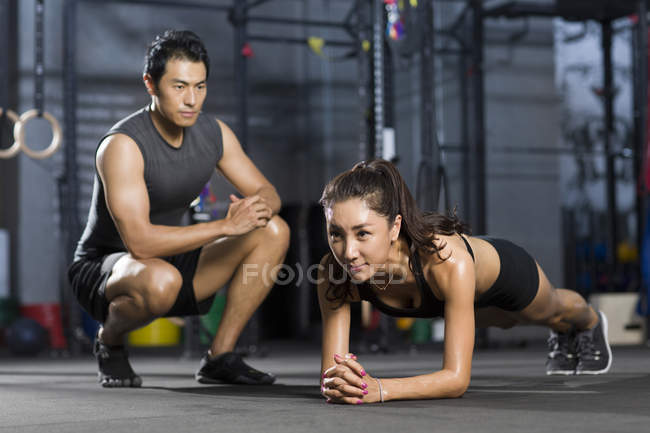Chinese woman working out with trainer in gym — Stock Photo