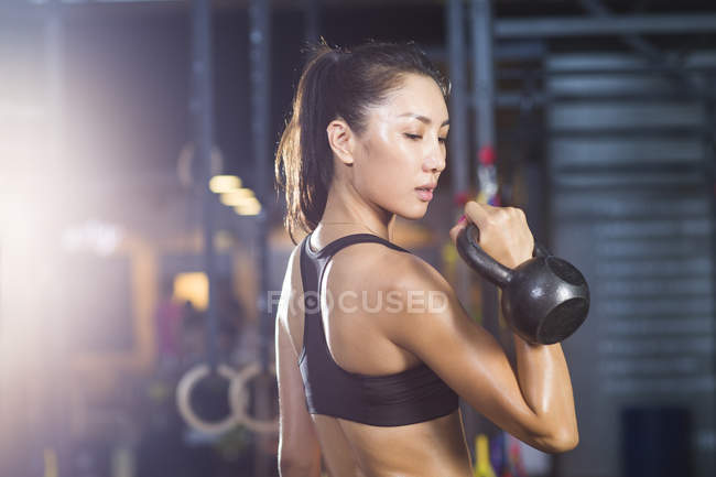 Chinese woman training with kettlebell in crossfit gym — Stock Photo