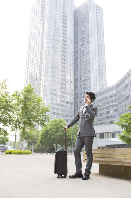 Chinese businessman talking on phone with suitcase — Stock Photo
