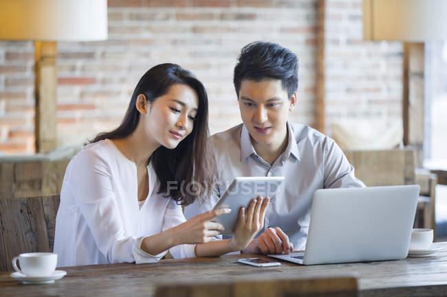 Uomo e donna cinese che utilizzano tablet e laptop digitali nel caffè — Foto stock