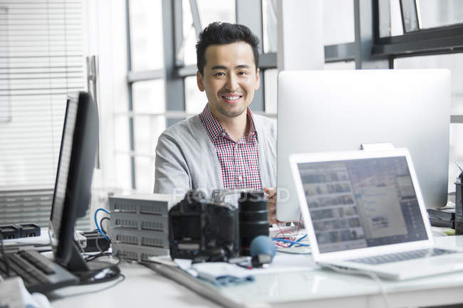 Chinese man sitting in office at computer desk — Stock Photo