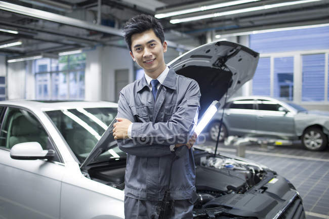 Chinese auto mechanic standing with flashlight in workshop — Stock Photo