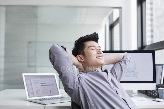 Chinese businessman resting with hands behind head — Stock Photo