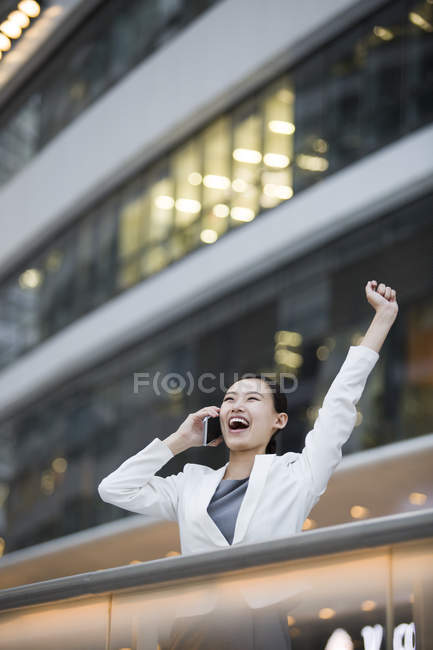 Chinese businesswoman talking on phone and cheering — Stock Photo