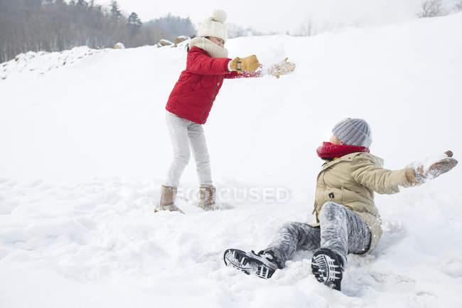 Crianças chinesas tendo bola de neve lutam no parque — Fotografia de Stock