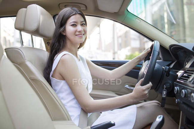 Chinese woman driving car and looking in camera — Stock Photo