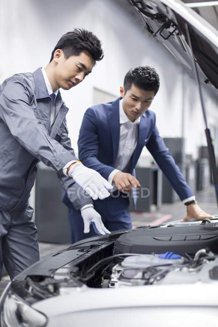 Chinese auto mechanic showing car engine to car owner — Stock Photo