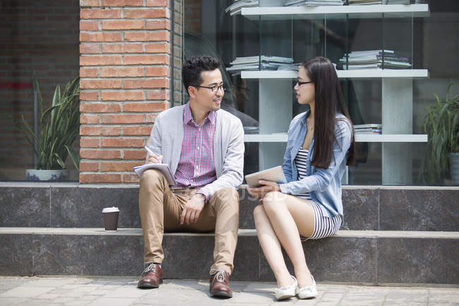 Chinese colleagues sitting and talking on street — Stock Photo