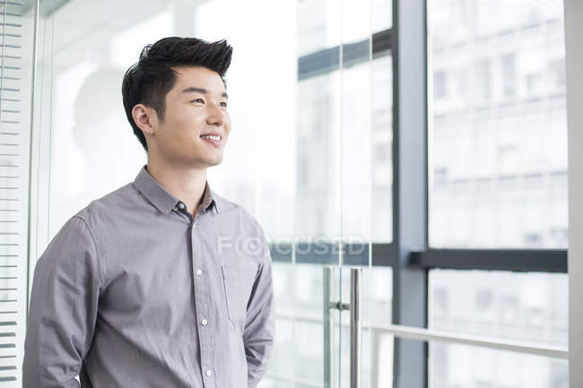 Chinese businessman looking away and smiling in office — Stock Photo