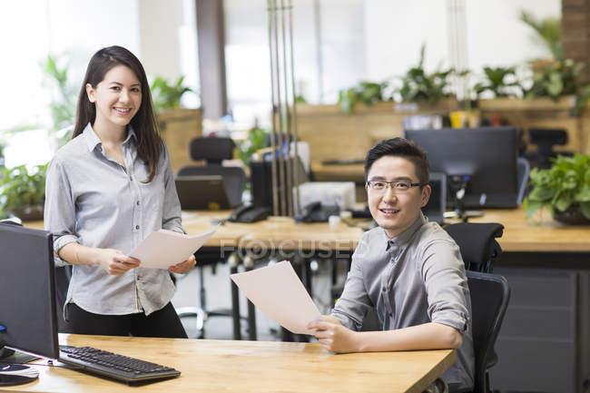 Des collègues chinois posant avec des papiers au bureau — Photo de stock