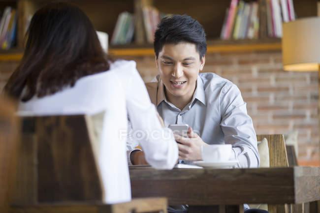 Donna cinese e l uomo seduto con lo smartphone in caffetteria — Foto stock