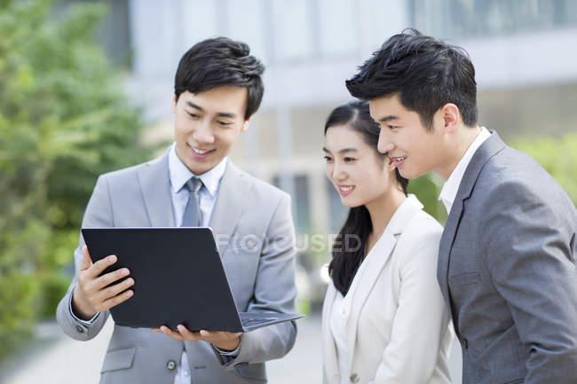 Uomini d'affari cinesi che lavorano con laptop sulla strada — Foto stock