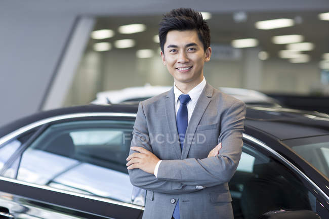 Chinese salesman standing in car showroom with arms folded — Stock Photo