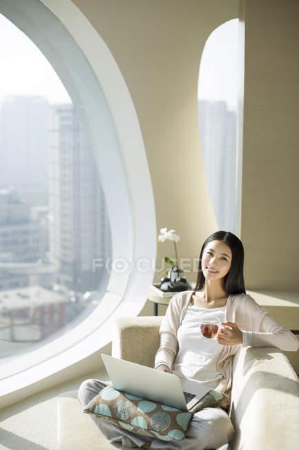 Donna cinese con tazza di tè utilizzando il computer portatile sul divano — Foto stock