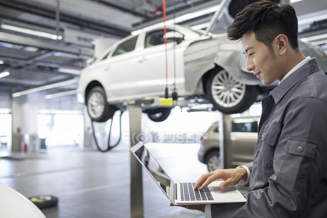 Chinesischen Kfz-Mechaniker mit Laptop in Werkstatt — Stockfoto