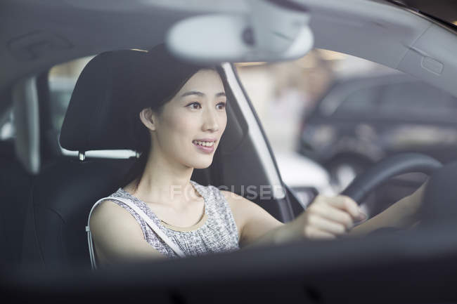 Chinese woman sitting in car and holding steering wheel — Stock Photo