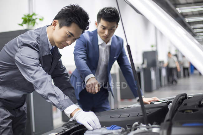 Chinese car owner showing engine to auto mechanic — Stock Photo