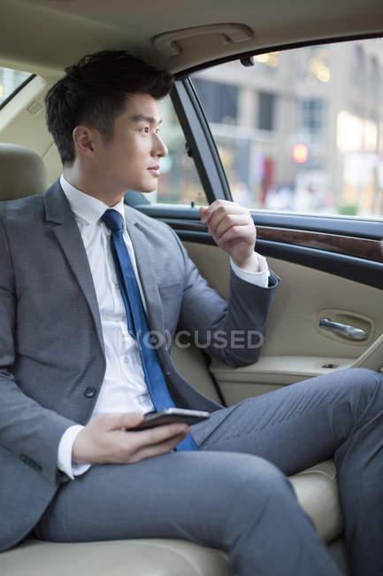 Chinese businessman sitting on car back seat — Stock Photo