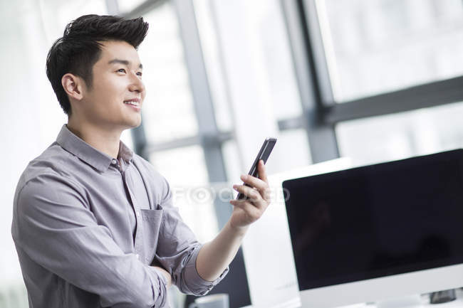 Chinese businessman holding smartphone in office — Stock Photo