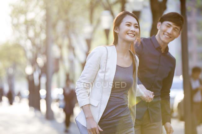 Chinesisches Paar hält Händchen, während es auf Bürgersteig geht — Stockfoto