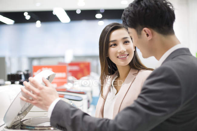 Chinese couple choosing multicooker in electronics store — Stock Photo