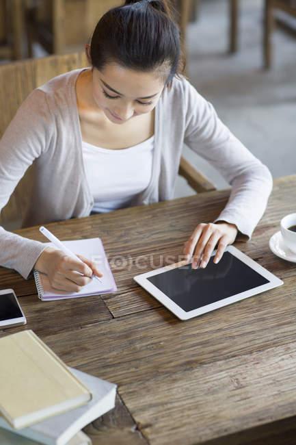 Mujer China estudiar en café con tableta digital - foto de stock