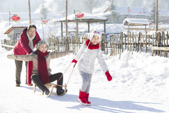 Meninas chinesas, puxando o trenó com os avós na neve — Fotografia de Stock