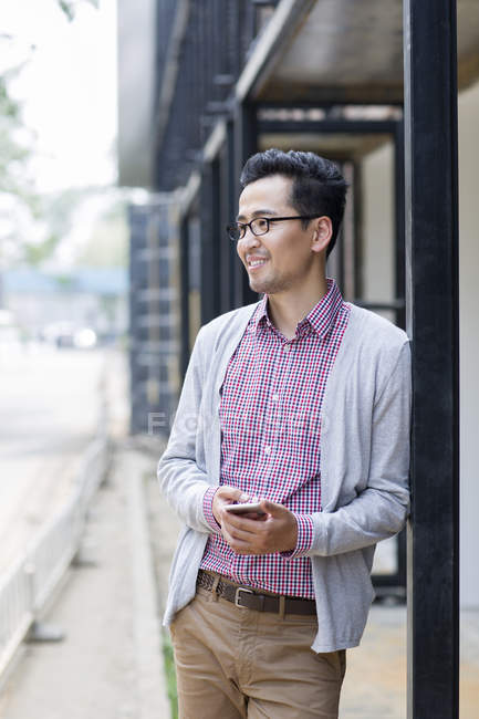 Chinese man standing on street and holding smartphone — Stock Photo