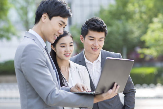 Chinese business people working with laptop at street — Stock Photo
