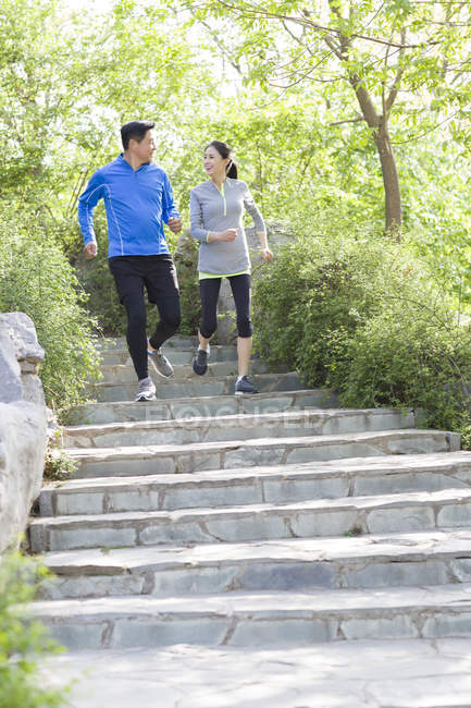 Chinese mature couple running on stairs in park — Stock Photo