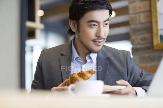 Uomo d'affari cinese seduto con croissant ed esaminando computer portatile — Foto stock