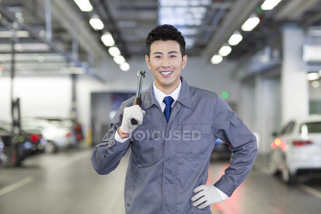 Chinese auto mechanic standing in workshop with tool — Stock Photo