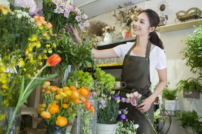 Женщина-флористка из Азии работает в цветочном магазине — стоковое фото