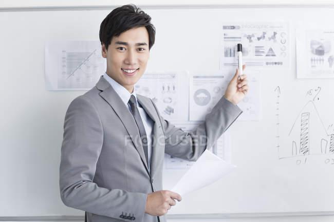 Homme d'affaires chinois montrant stratégie sur tableau blanc au bureau — Photo de stock