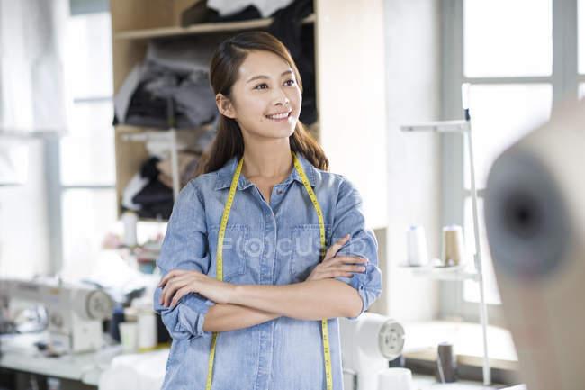 Diseñadora de moda china de pie con los brazos cruzados en el taller - foto de stock