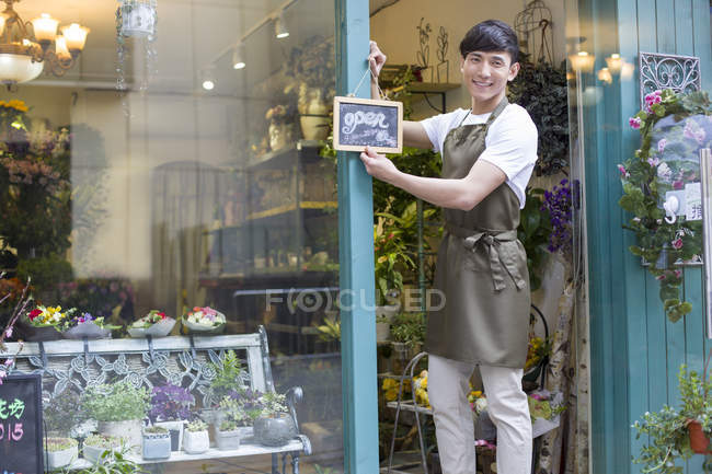 Chinese florist holding open sign in store doorway — Stock Photo