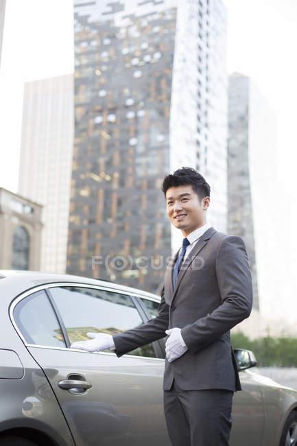 Chófer chino haciendo gesto de bienvenida en el coche - foto de stock