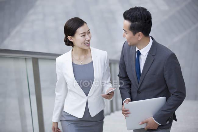 Uomini d'affari cinesi che camminano sulle scale e parlano — Foto stock