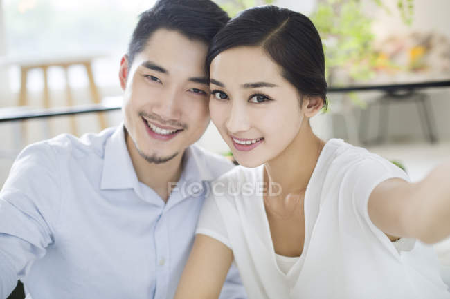 Chinese couple sitting cheek to cheek in cafe — Stock Photo