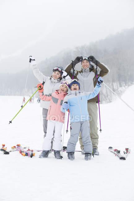 Китайская семья позирует на горнолыжном курорте с лыжные палки — стоковое фото
