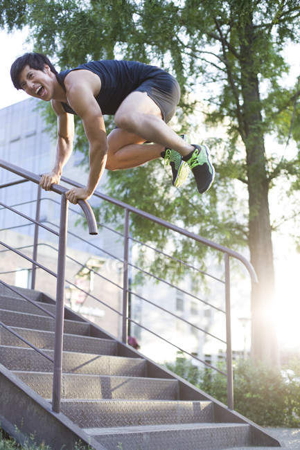 Chinese free runner jumping over balustrade — Stock Photo